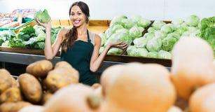 卖新鲜的莴苣的围裙的微笑的妇女 免版税库存图片