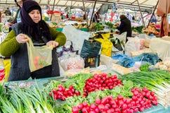 卖新鲜蔬菜的夫人在市场上 免版税图库摄影