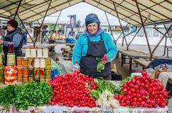 卖新鲜蔬菜的夫人在市场上 免版税库存照片