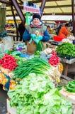 卖新鲜蔬菜的夫人在市场上 免版税库存图片
