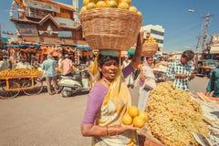 卖新鲜水果和桔子在室外市场上的妇女在繁忙的亚洲街道上 免版税库存照片