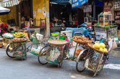 卖果子的各种各样的类型从他们的自行车的摊贩在河内 免版税库存图片