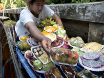 卖果子的妇女在浮动市场曼谷上 免版税库存图片