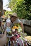 卖果子的妇女在浮动市场曼谷上 库存图片