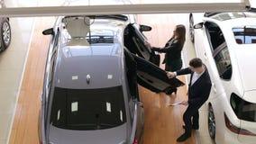 卖汽车的专业推销员对美丽的女性买家在售车行 股票录像