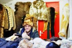 卖温暖的衣裳的微笑的拉脱维亚人在里加圣诞节市场上 库存图片