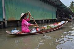 卖热带水果附近的浮动市场的小船供营商在曼谷地区附近 免版税库存照片