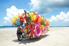 卖玩具的人乘驾流动商店对海滩的孩子在东泰国 免版税库存照片