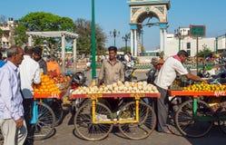 卖瓜和普通话在拥挤的街市场上的水果和蔬菜贸易商 免版税库存照片