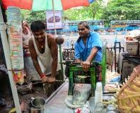 卖甘蔗汁的人们在市场上在加尔各答,印度 图库摄影