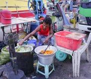 卖甜点的缅甸妇女在市场上结块 库存照片