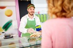卖甜点的面包点心店的供营商对costumer 免版税库存照片