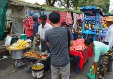 卖甜玉米、裁减红色西瓜和素食主义者油炸馅饼的摊贩对顾客 库存图片