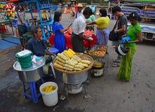 卖甜玉米、裁减红色西瓜和素食主义者油炸馅饼的路旁供营商 免版税图库摄影