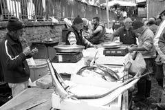 卖箭鱼的渔夫对鱼市在卡塔尼亚,意大利 免版税库存图片