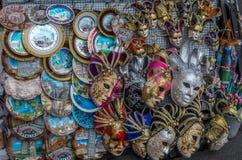卖纪念品当狂欢节面具和板材的街道立场的特写镜头在比萨,意大利 免版税库存图片