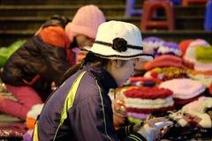 卖羊毛衣物的未认出的妇女在夜市场上在大叻,越南 库存图片