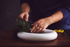卖花人做一个传统圣诞节花圈 库存照片