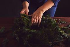 卖花人做一个传统圣诞节花圈 免版税图库摄影