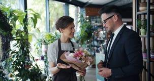 卖花人和顾客的慢动作谈话在花店藏品花束 股票视频