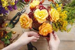 卖花人在工作:做花束的妇女橙色玫瑰和秋天 免版税图库摄影