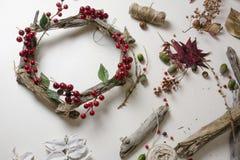 卖花人在工作:创造一个木花圈用圣诞节红色莓果 库存图片