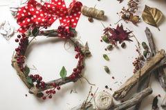 卖花人在工作:创造一个木花圈用圣诞节红色barries 免版税库存照片