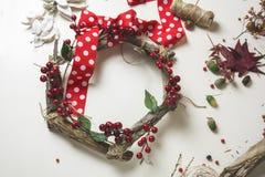 卖花人在工作:创造一个木花圈用圣诞节红色barries 库存图片