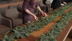 卖花人在工作:妇女递做圣诞节装饰诗歌选冷杉Nobilis 新年好晚餐宴餐 股票视频