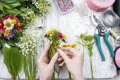 卖花人在工作 做花束的妇女野花 免版税库存照片