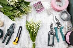 卖花人在工作 做花束的妇女铃兰流程 免版税库存照片