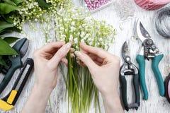 卖花人在工作 做花束的妇女铃兰流程 库存图片