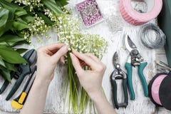 卖花人在工作 做花束的妇女铃兰流程 库存照片