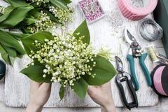卖花人在工作 做花束的妇女铃兰流程 图库摄影