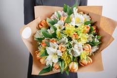 卖花人在工作 白色和橙色郁金香德国锥脚形酒杯花束  葡萄酒植物的背景,五颜六色的玫瑰,古董 免版税库存图片