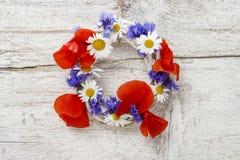 卖花人在工作 装饰与野花的妇女柳条花圈 免版税库存图片