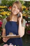 卖花人在拿着剪贴板的商店接受电话命令 免版税库存照片