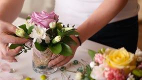 卖花人女孩收集玫瑰和其他花好的小的花束在一个小花瓶 免版税图库摄影