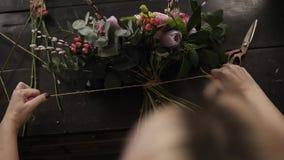 卖花人装饰的花美丽的花束在桌上说谎 女孩紧紧拉紧它与在的绳索 股票视频