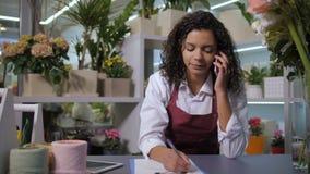 卖花人谈话在有客户的电话花店的 股票视频