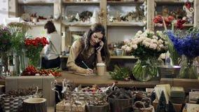 卖花人谈话由电话和做在笔记本的笔记,杯子在笔记本附近站立 股票录像