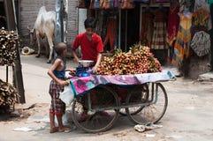 卖荔枝果子的男孩在新德里街道  免版税库存图片