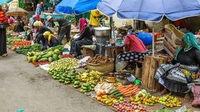 卖蔬菜和水果在街道上的小组可怜的妇女 图库摄影