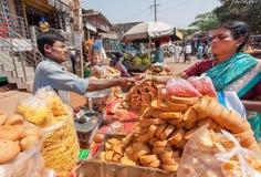 卖薄脆饼干甜点、饼和面包的贸易商对在卡纳塔克邦状态拥挤的街上的印地安妇女  免版税库存图片