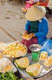 卖被清洗的和被包装的留连果的骨肉亚裔妇女 库存照片