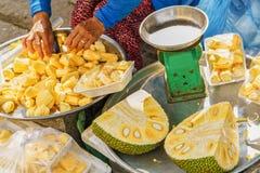 卖被清洗的留连果的骨肉亚裔妇女在会安市 免版税库存照片
