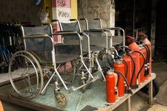 卖轮椅和灭火器有红色管照片的商店拍在德波印度尼西亚 免版税库存照片