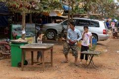 卖辣辣椒壳的小女孩在街道 库存照片