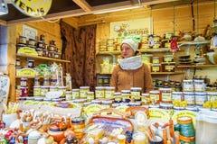 卖陶瓷和蜂蜜的少妇在圣诞节市场上 免版税图库摄影