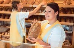卖面包和其他产品的两个女售货员在面包店购物 免版税图库摄影